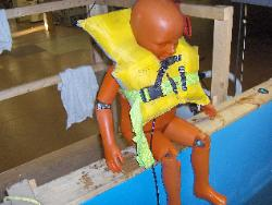 Child flotation manikin on seat above test tank